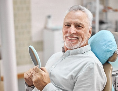 Happy patient at appointment to use dental insurance benefits
