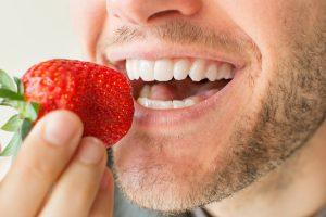 man white teeth strawberries