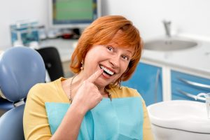 woman pointing to her tooth