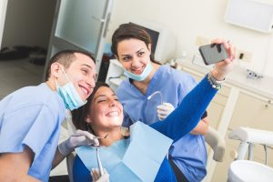 happy patient taking selfie at dentist