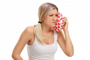 woman holding cold compress to face