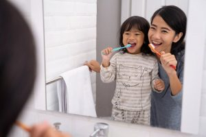 parent and a child brushing their teeth together in the bathroom
