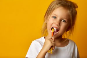 little girl brushing her teeth against yellow-orange background