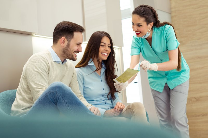 Dental assistant talking to couple in dental office