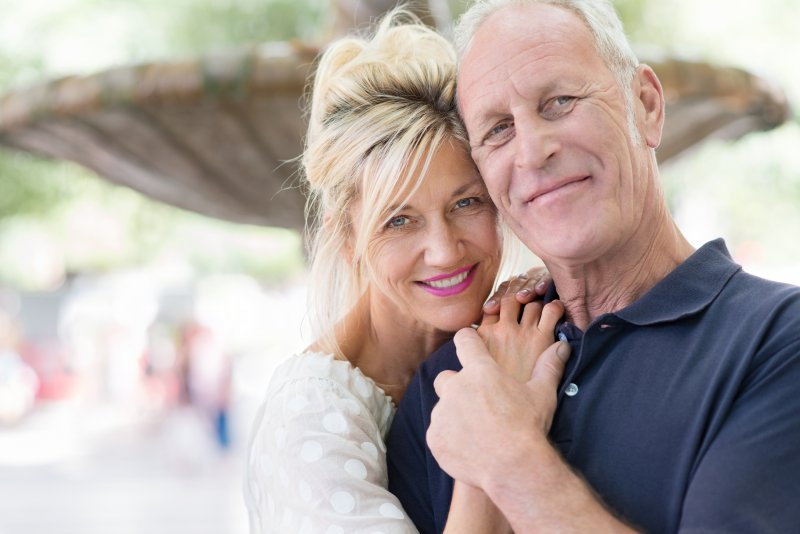 a middle-aged man and woman hugging and smiling after receiving dental implants in Superior